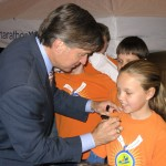Will Wynn autographs the t-shirt of a MarathonKids runner.